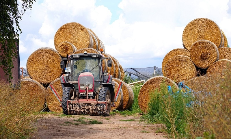 tractor working on bales of hay
