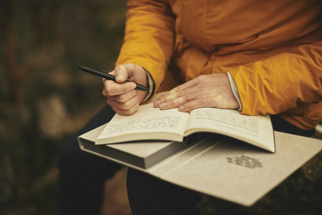 person writing a journal