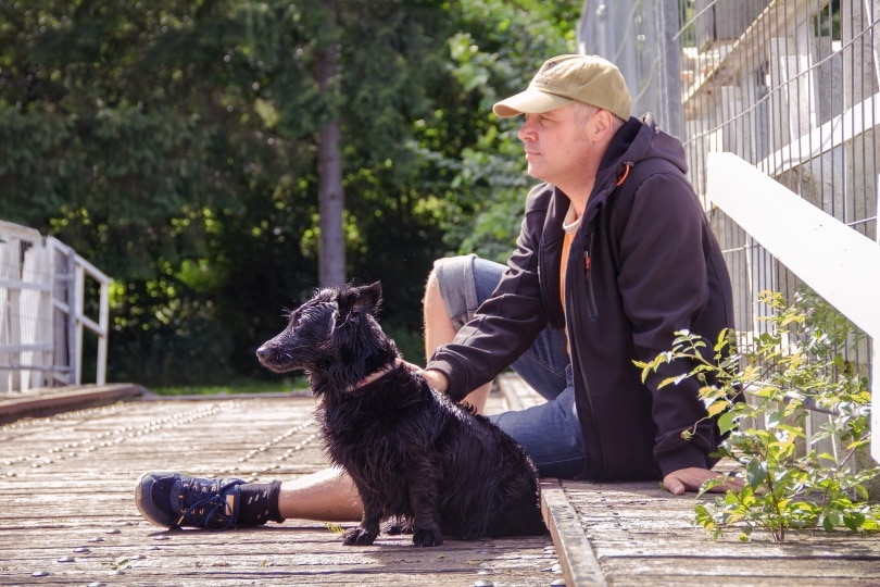 pet owner sitting beside his dog